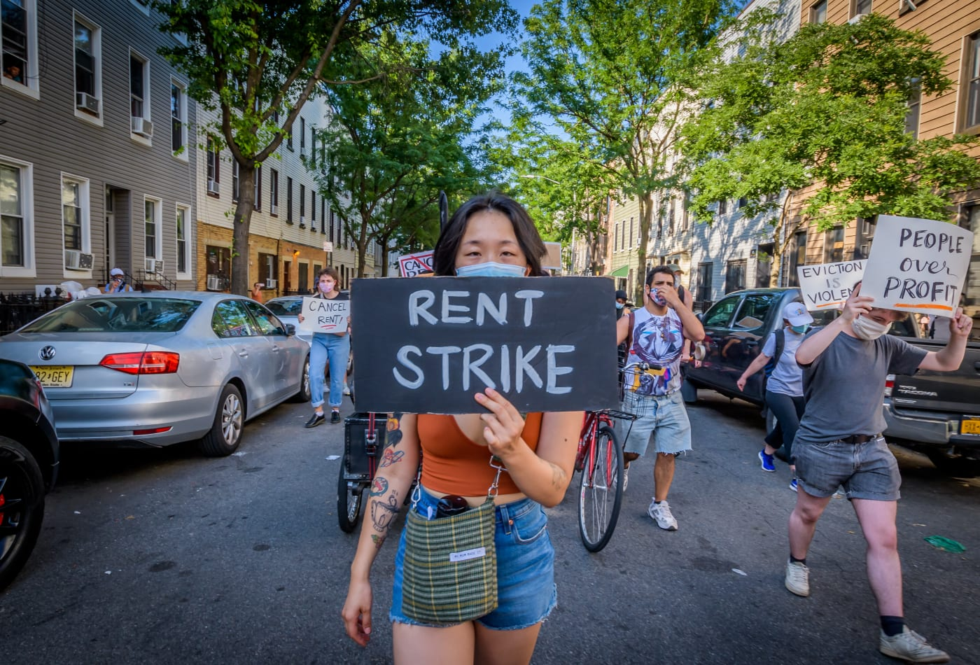 Image of woman holding up a rent strike sign in a demonstration, people are marching down a street in Brooklyn