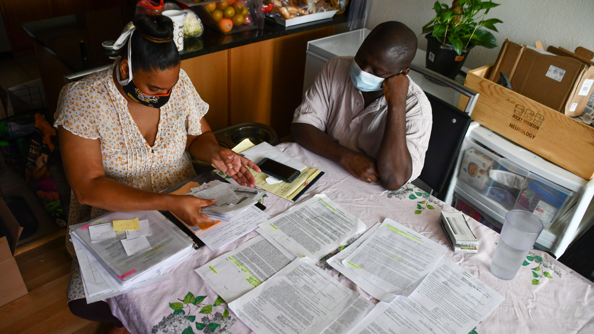 Two Black people wearing masks look through documents at their kitchen table