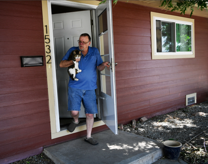 Man walking out of his house holding his cat