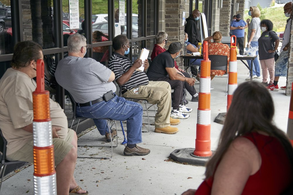 A seated line of people in masks wait outside an unemployment office