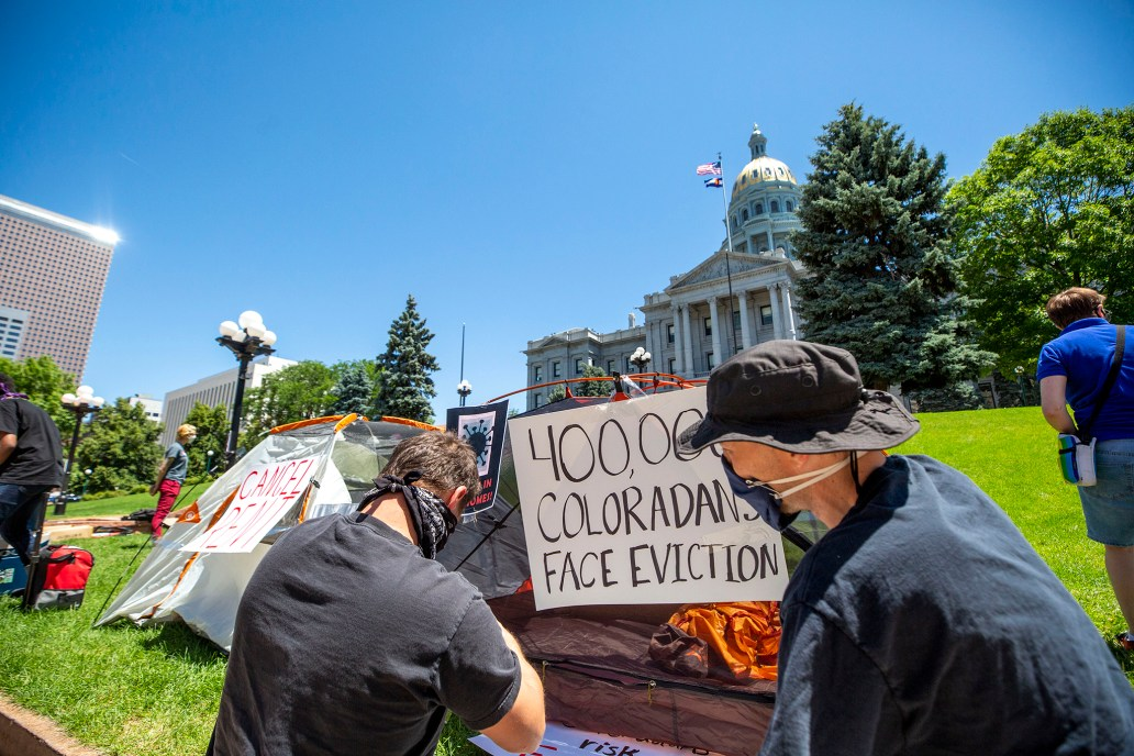 """A group of protestors against evictions in Colorado camping outside Denver Capitol Hill; signs read """"400,000 Coloradans face eviction"""" and """"cancel rent"""""""