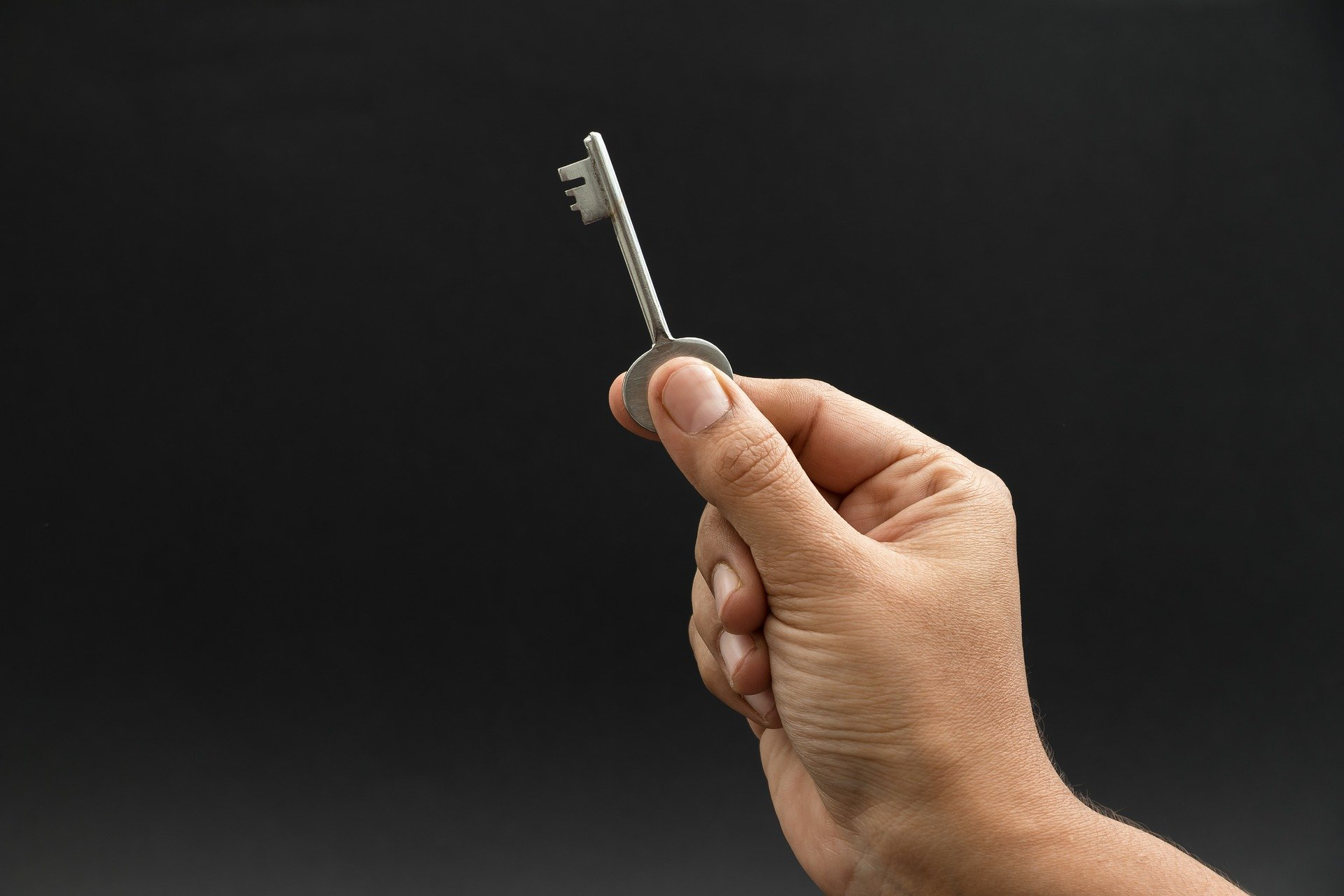 A hand holding up a key
