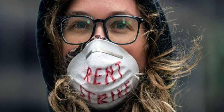 """A white woman wears a mask with """"rent strike"""" written in red"""