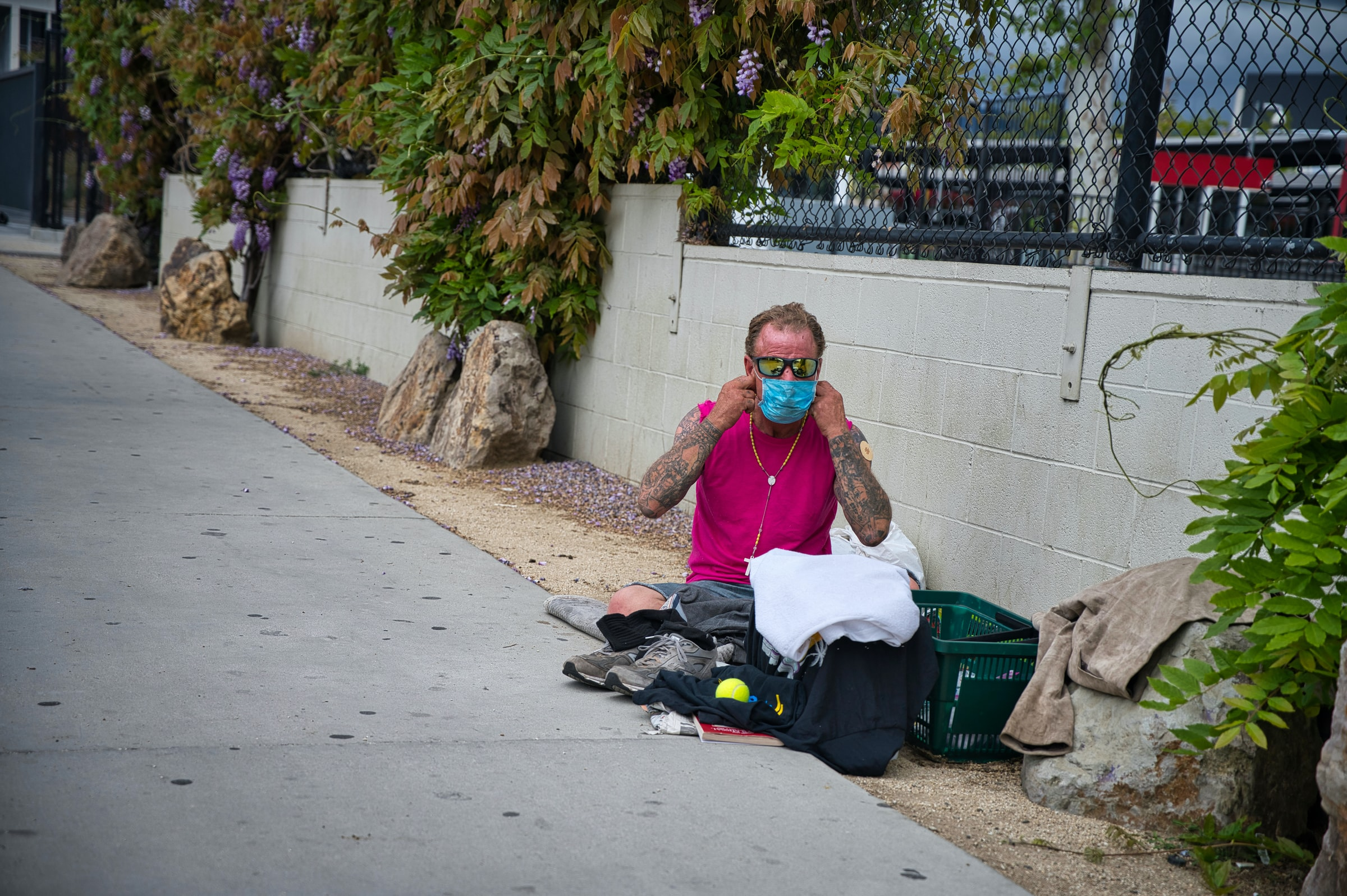 A man in a mask sits on the side of a road with a basket of belongings