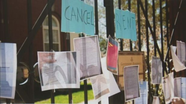 """Fence post with """"cancel rent"""" signs and photos of eviction notices"""