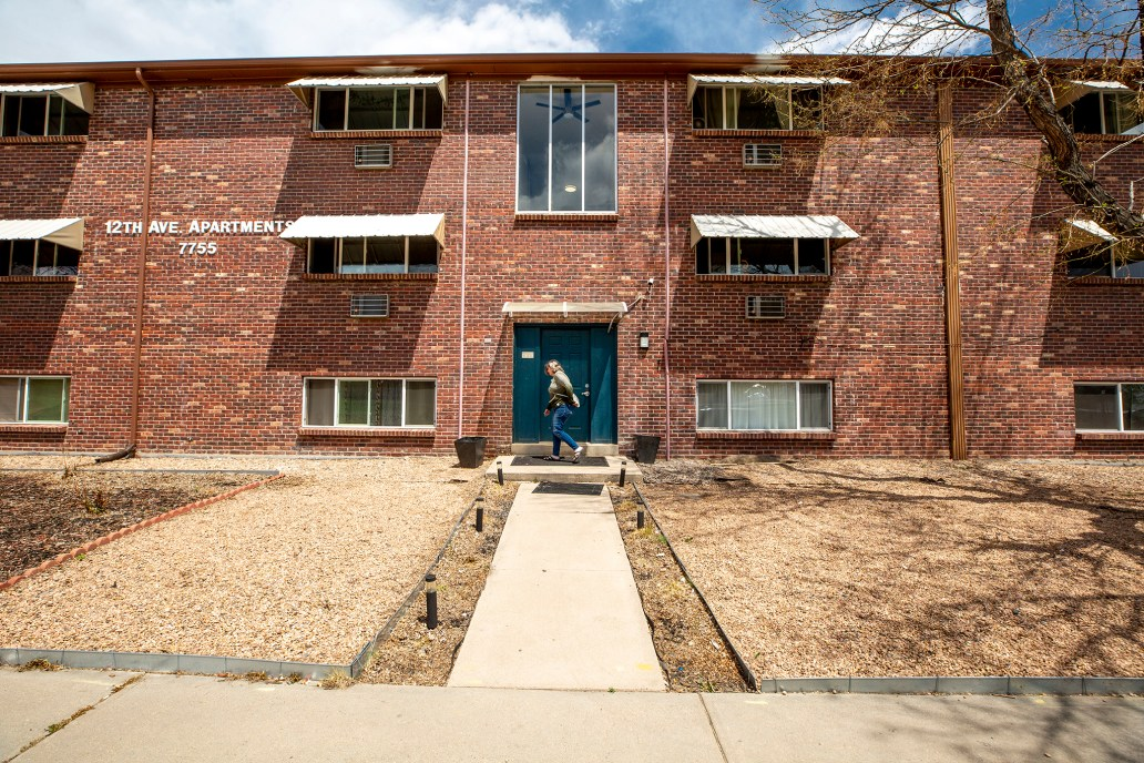 A woman stands in front of an apartment building