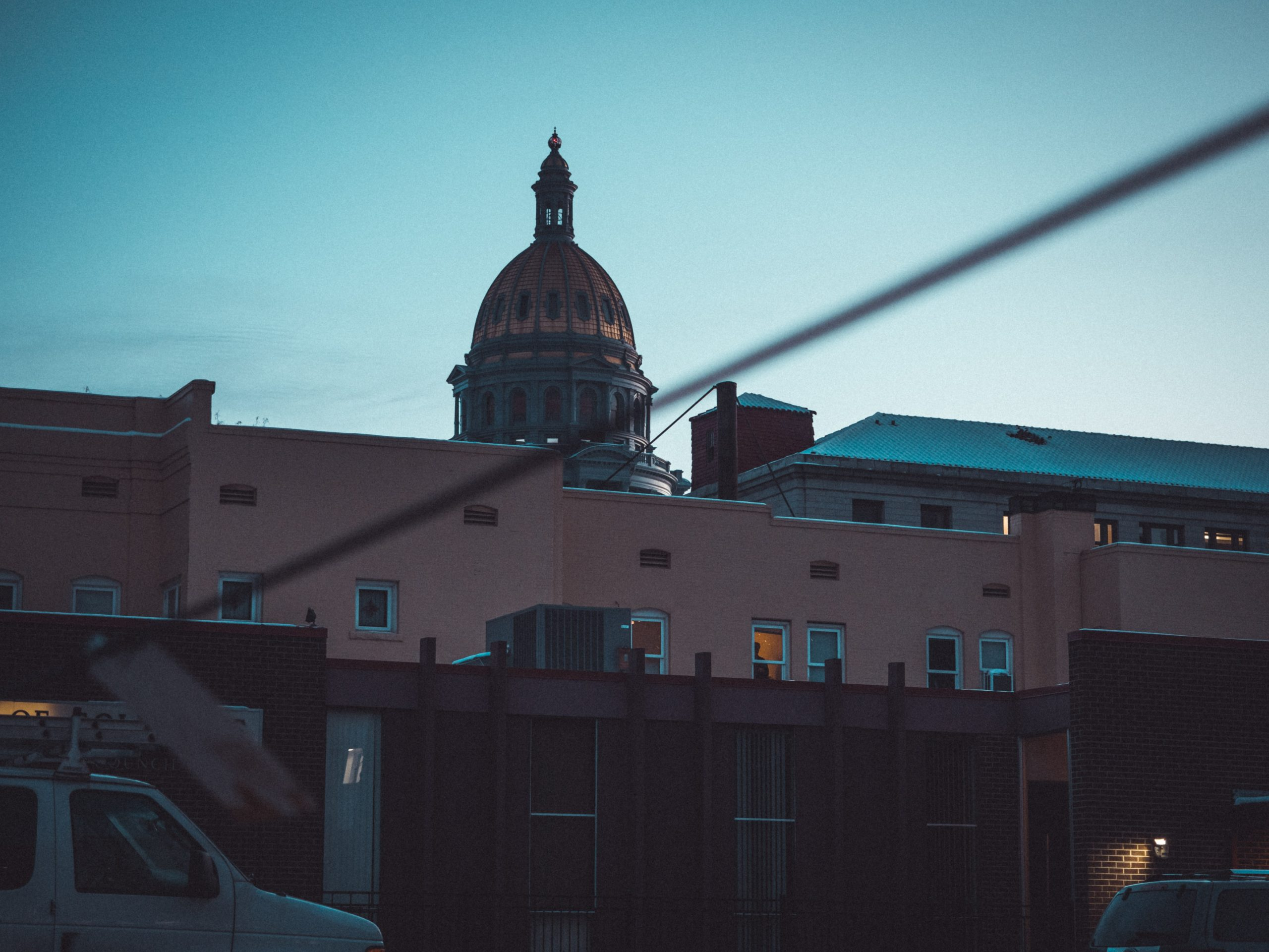 The dome of the Denver State Capitol Building as seen behind apartment buildings