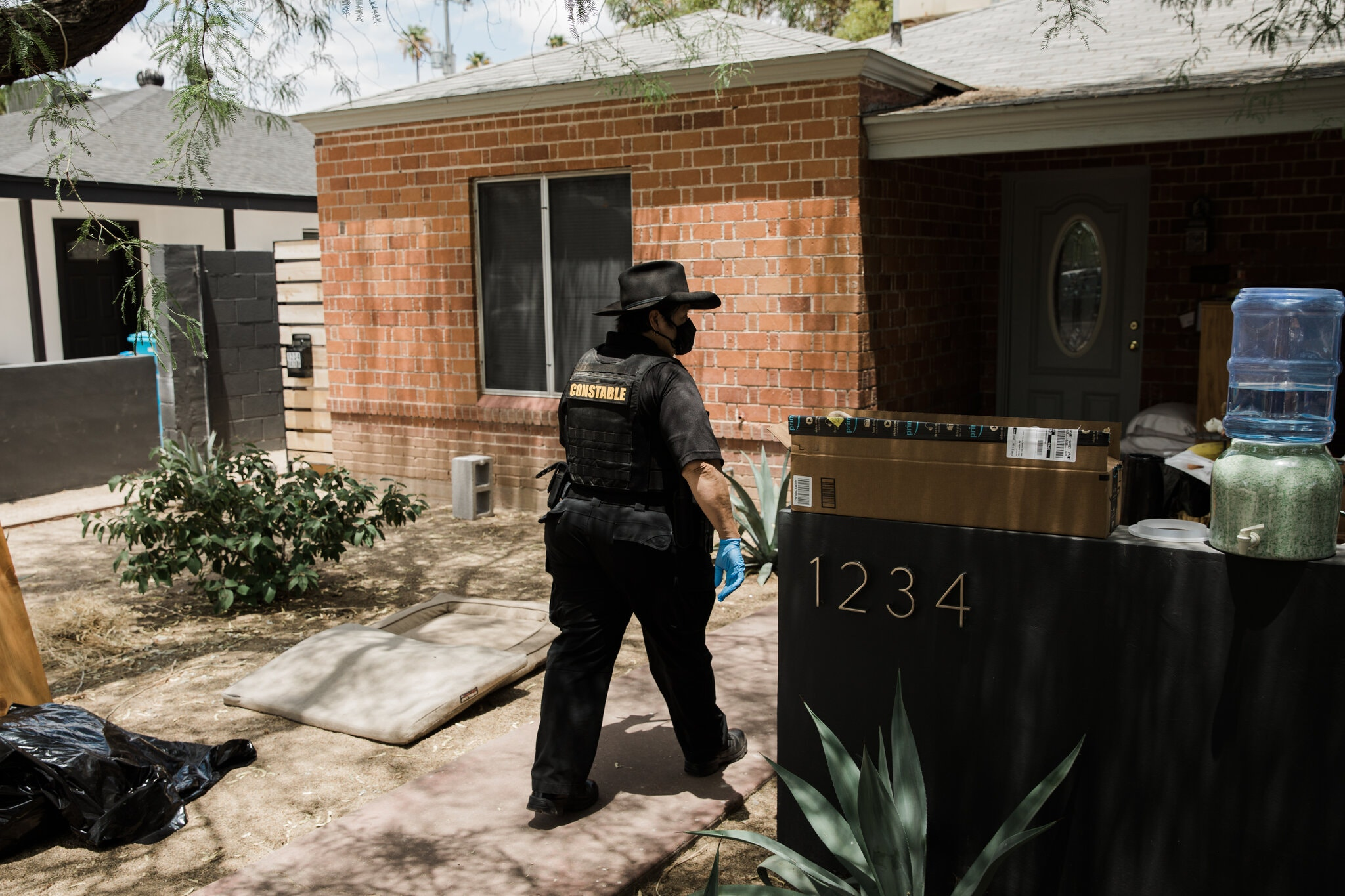 A constable with a mask and gloves walks towards a home preparing to serve an eviction notice