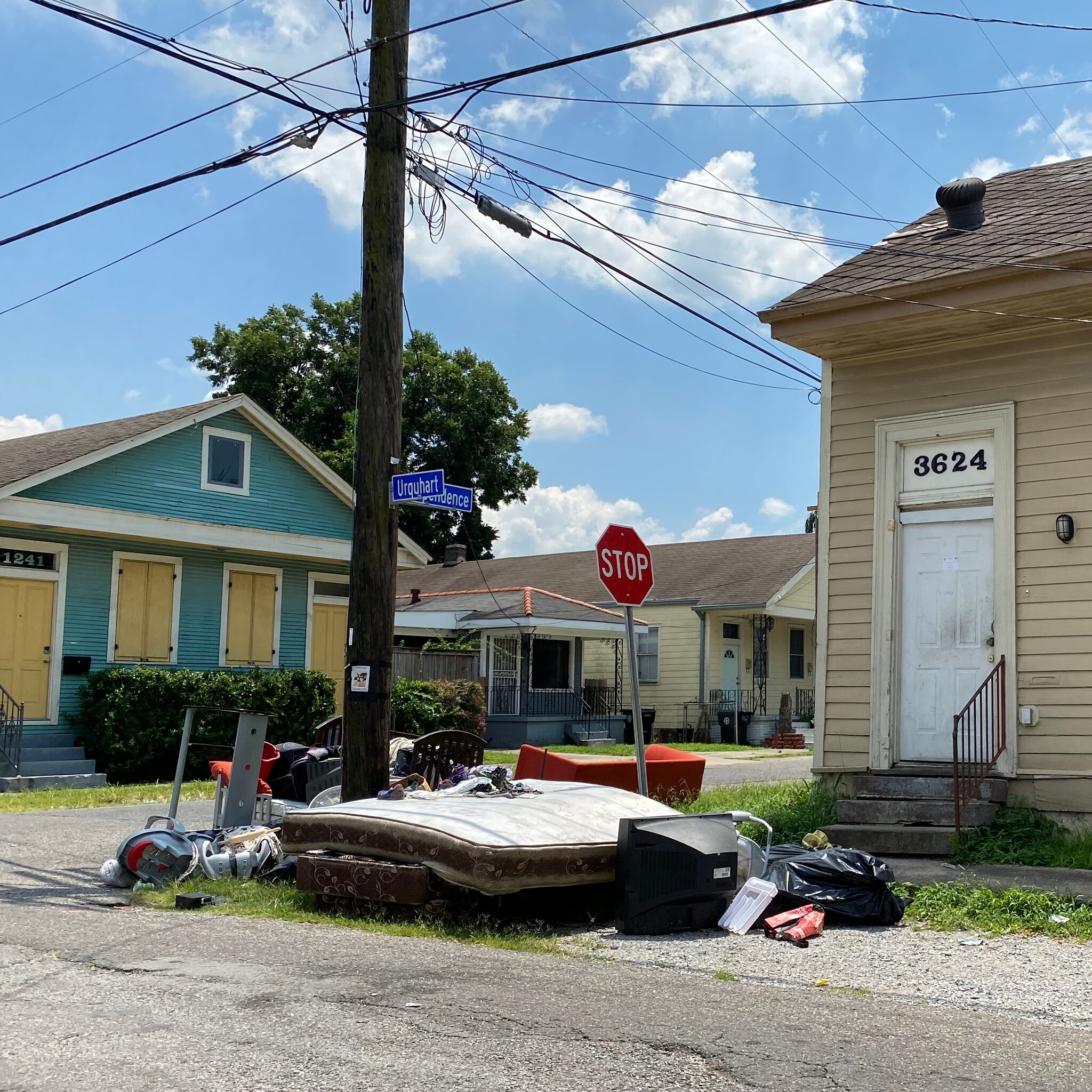 A pile of household items and belongings on the side of the road.