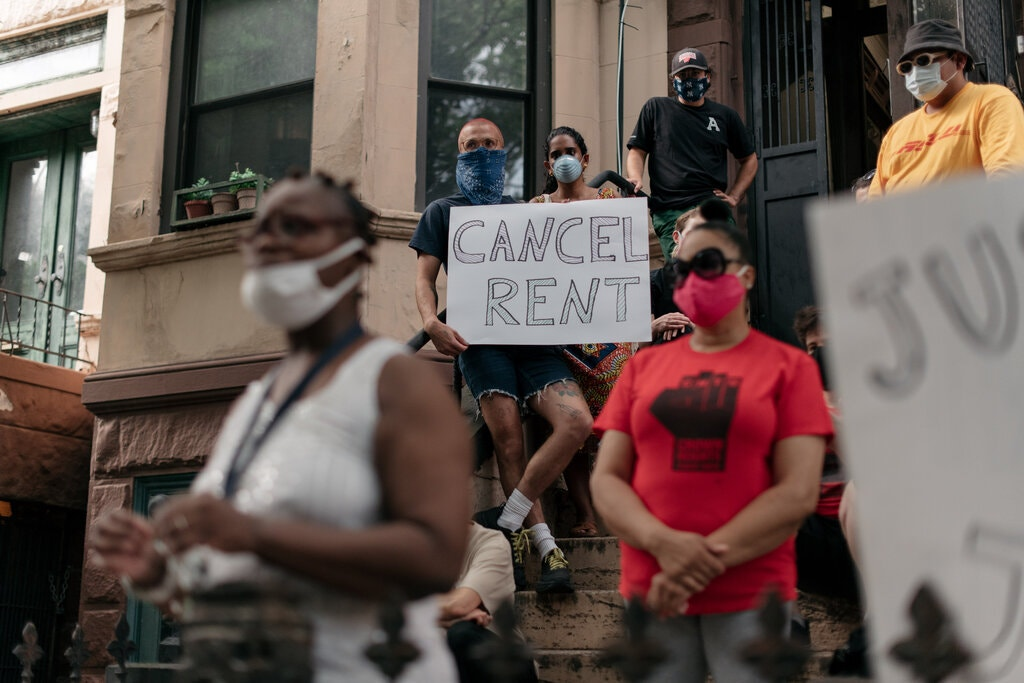 """A group of people in masks gather with """"cancel rent"""" signs on a stoop in Brooklyn, NY."""