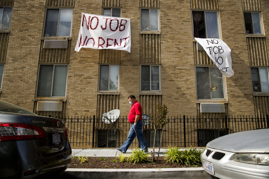 """Man walking on sidewalk outside an apartment building with """"No Job, No Rent"""" signs in the windows"""