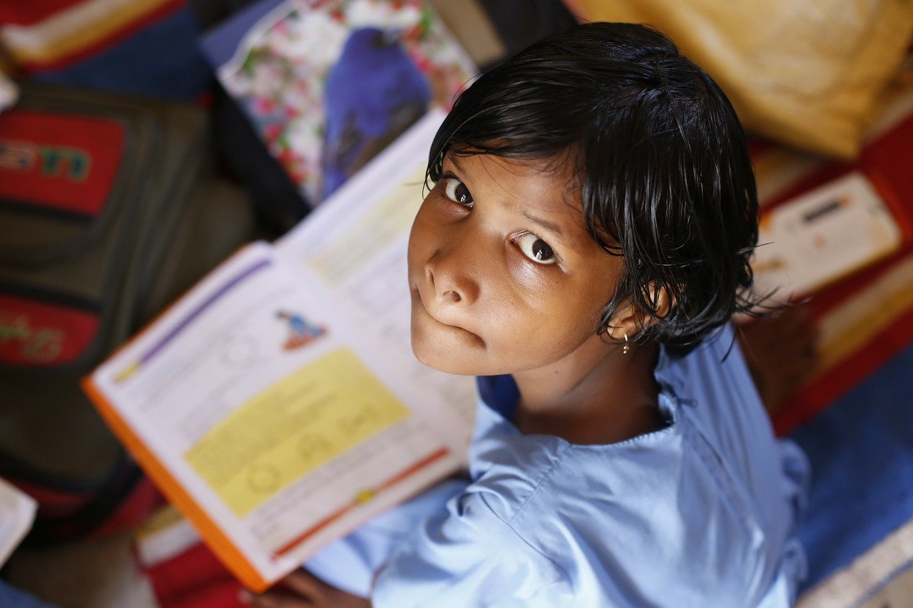 Image of a child with a textbook looking up at the camera