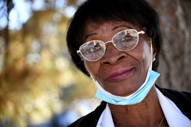 Serah Ezeudoye smiles in front of her apartment in Denver, CO, a mask beneath her chin.