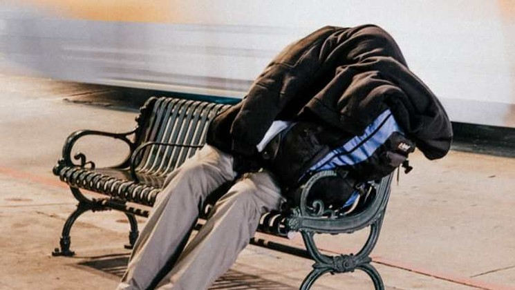 Image of a homeless person sleeping on a bench.