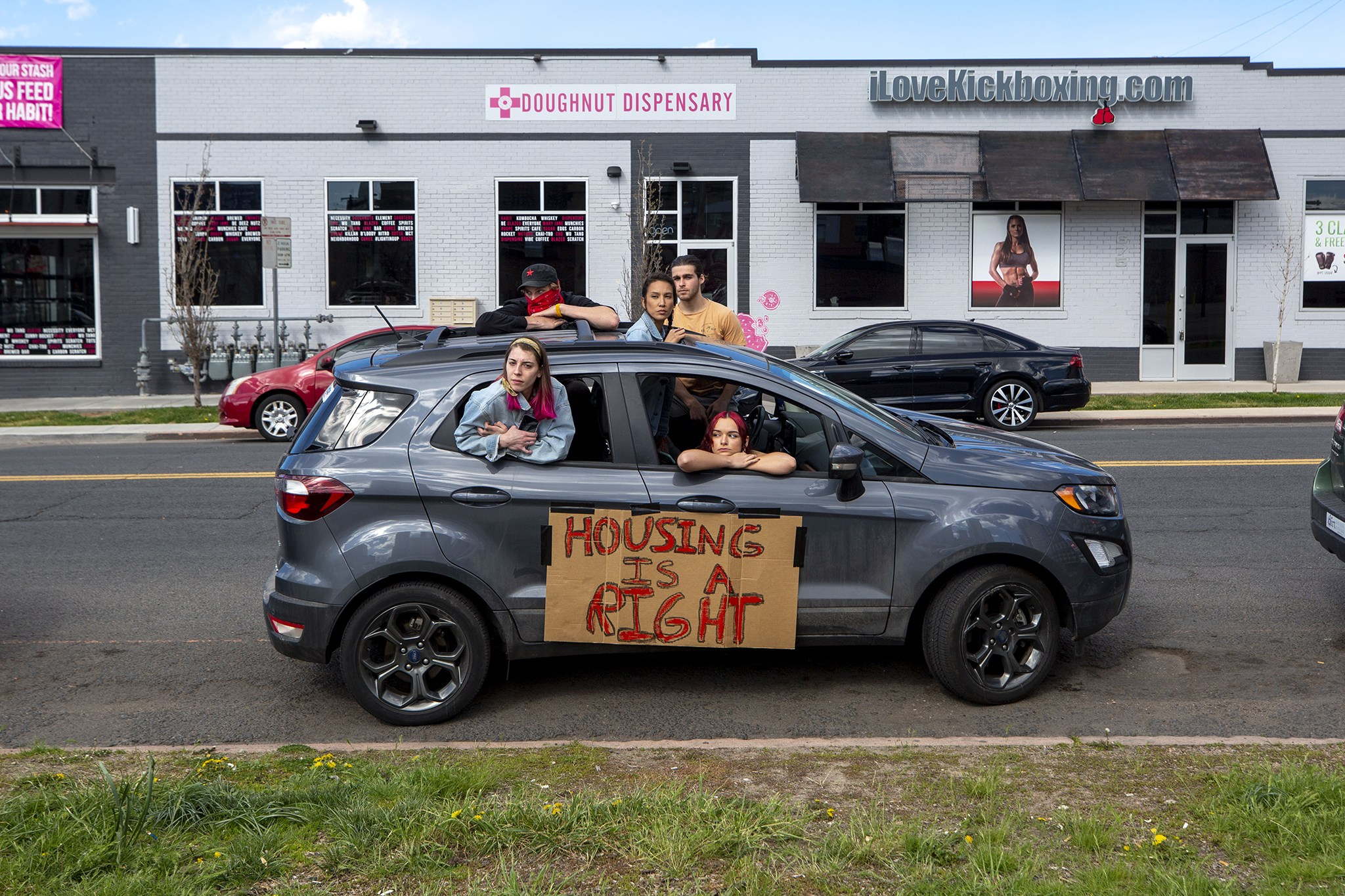 """Image of protestors in a caravan with a sign on the vehicle reading: """"Housing is a Right"""""""