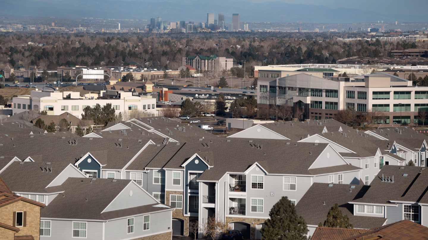 Image of housing in the foreground with Denver skyline in the distance