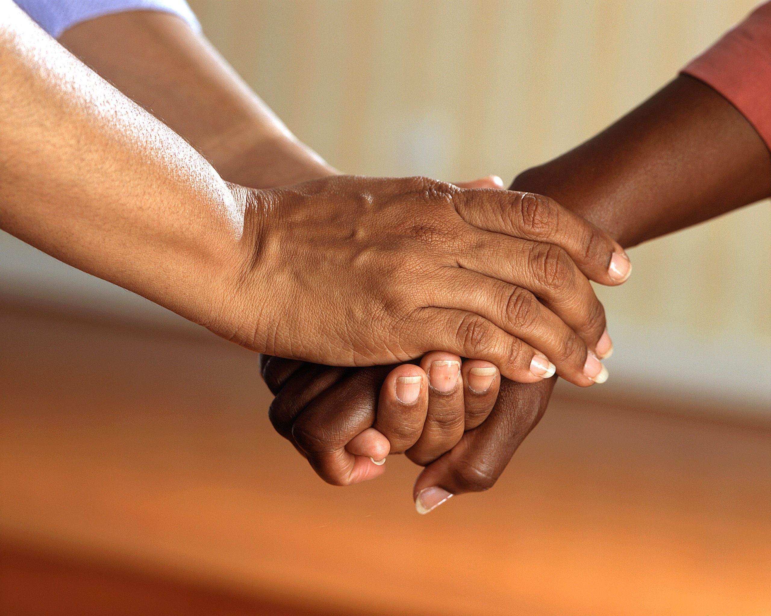 Image of two Black women holding hands.